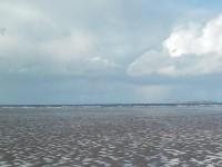 Une plage à marée basse découvrant sa nudité et le flot qui s'éloigne.