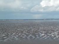 La grève s'étend toujours à marée basse et l'azur s'embrume tandis que s'éloigne le flot.