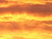 Ciel aux nuages dorés par un coucher de soleil contemplé par un homme et une femme